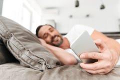 Homem maduro de sorriso que usa o telefone celular ao descansar foto de stock royalty free