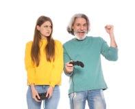 Homem maduro e jovem mulher que jogam jogos de v?deo com os controladores isolados fotografia de stock royalty free