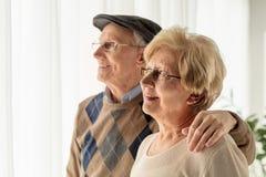 Homem maduro e mulher que olham através de uma janela fotografia de stock royalty free