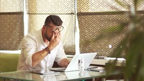 Homem maduro em uma camisa branca e funcionamento puro da barba duramente no escritório no computador Avral no trabalho, fim do p video estoque
