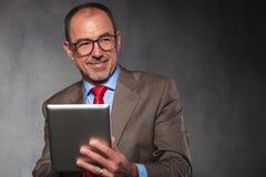 Homem maduro em vidros vestindo do terno, usando sua tabuleta Fotografia de Stock Royalty Free