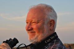 Homem maduro feliz com os binóculos no por do sol Imagens de Stock