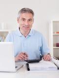 Homem maduro feliz que calcula Fotografia de Stock