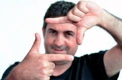 Homem maduro feliz que cria o quadro com os dedos Imagem de Stock Royalty Free