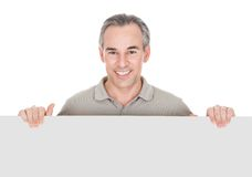 Homem maduro feliz que está atrás do cartaz Fotos de Stock Royalty Free