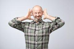 Homem maduro irritado que obstrui as orelhas com dedos fotografia de stock