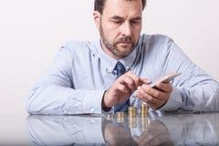 Homem maduro na mesa com as euro- moedas empilhadas Fotos de Stock