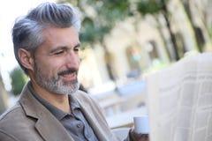 Homem maduro no café da cidade e no jornal bebendo da leitura fotografia de stock