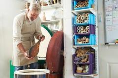 Homem maduro no vaso do acendimento do estúdio da cerâmica na estufa fotos de stock royalty free