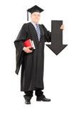 Homem maduro no vestido da graduação que guarda a seta grande que aponta para baixo Foto de Stock Royalty Free