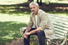 Homem maduro pensativo que senta-se no banco em um parque urbano Fotografia de Stock