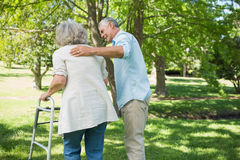 Homem maduro que ajuda à mulher com o caminhante no parque foto de stock