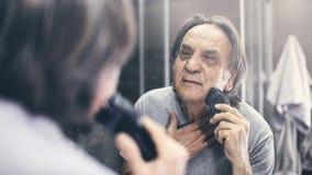 Homem maduro que barbeia na frente do espelho imagens de stock royalty free