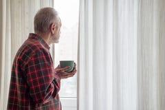 Homem maduro que bebe seu café e que olha fora da janela imagens de stock