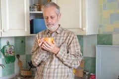 Homem maduro que bebe seu café na cozinha imagem de stock