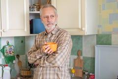 Homem maduro que bebe seu café na cozinha imagem de stock royalty free