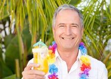 Homem maduro que bebe um cocktail sob o sol imagem de stock royalty free