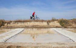 Homem maduro que biking ao lado do saltworks de Isla Cristina, Espanha Imagens de Stock