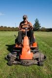 Homem maduro que conduz o cortador de grama Fotografia de Stock