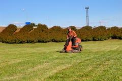 Homem maduro que conduz o cortador de grama Imagem de Stock