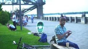 Homem maduro que consulta na tabuleta digital, sentando-se no banco em um parque vídeos de arquivo