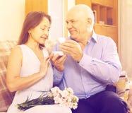 Homem maduro que dá a mulher a caixa de joia fotografia de stock royalty free