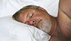 Homem maduro que dorme pacificamente imagem de stock