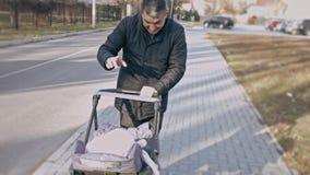 Homem maduro que empurra o carrinho de criança de bebê e que joga com neta do bebê Passeio em um dia de mola bonito Avô e vídeos de arquivo
