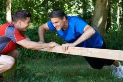 Homem maduro que exercita com instrutor pessoal In Park imagens de stock