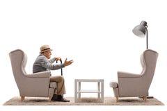 Homem maduro que fala com uma poltrona vazia Fotografia de Stock Royalty Free