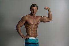 Homem maduro que faz o exercício para o bíceps em Grey Background Foto de Stock