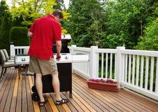 Homem maduro que gira sobre a grade do barbecu quando parte externa na plataforma aberta Imagem de Stock Royalty Free