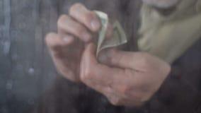 Homem maduro que guarda à disposição os últimos dólares, calculando o orçamento, utilidades caras vídeos de arquivo