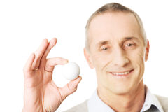 Homem maduro que guarda a bola de golfe Imagem de Stock Royalty Free