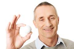 Homem maduro que guarda a bola de golfe Imagens de Stock