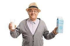 Homem maduro que guarda um vidro do leite e de uma caixa do leite fotografia de stock