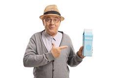 Homem maduro que guarda uma caixa e apontar do leite fotografia de stock