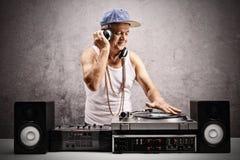 Homem maduro que joga a música em uma plataforma giratória imagem de stock royalty free