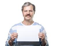 Homem maduro que mantem um quadro de avisos em branco isolado foto de stock