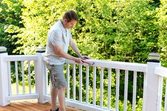 Homem maduro que martela o prego nos trilhos brancos da plataforma exterior foto de stock