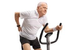 Homem maduro que monta uma bicicleta de exercício e que experimenta a dor nas costas Imagens de Stock Royalty Free