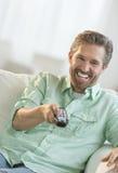 Homem maduro que olha a tevê no sofá foto de stock royalty free