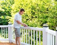 Homem maduro que raspa a pintura velha da plataforma exterior fotos de stock