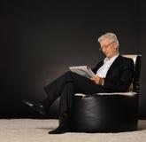 Homem maduro que senta-se com jornal foto de stock