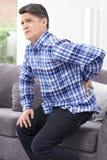 Homem maduro que sofre da dor lombar em casa foto de stock royalty free