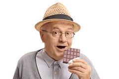 Homem maduro que tem uma mordida fora de uma barra de chocolate fotografia de stock