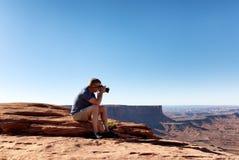 Homem maduro que toma fotos de Grand Canyon ao sentar-se para baixo foto de stock royalty free