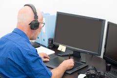 Homem maduro que trabalha em sua tabuleta de gráficos imagem de stock