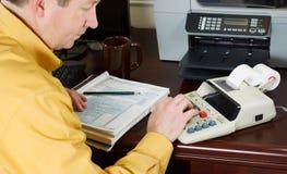 Homem maduro que trabalha os números em seus imposto sobre rendimento imagens de stock