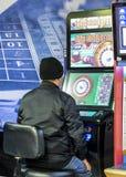 Homem maduro que usa máquina fixa da roleta das probabilidades nos editores Londres, Inglaterra, Reino Unido Máquina descrita com imagens de stock